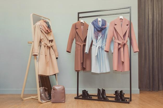 レールの上のカラフルな女性のコートとネックピース。