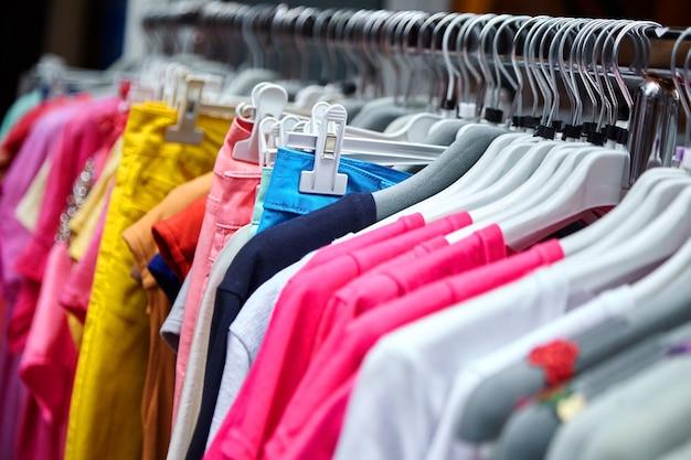 Красочные женские летние брюки и футболки на вешалках