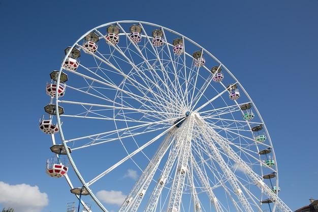 Colorful ferris wheel against blue summer sky background