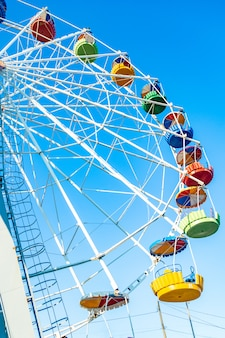 Colorful ferris wheel of the amusement park in the blue sky
