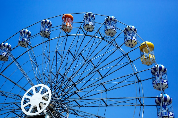 The colorful ferris wheel on the blue sky background.