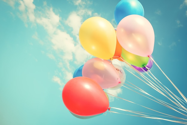 Colorful festive balloons over blue sky with a retro vintage instagram filter effect.