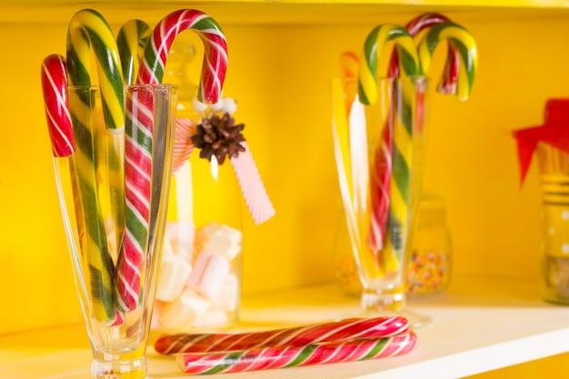 クリスマスやホリデーシーズンやパーティーを祝うために明るい黄色の棚に表示されるガラスの瓶にカラフルなお祝いのキャンディケイン