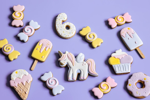 Colorful festive gingerbread cookies of different shapes covered with glaze.
