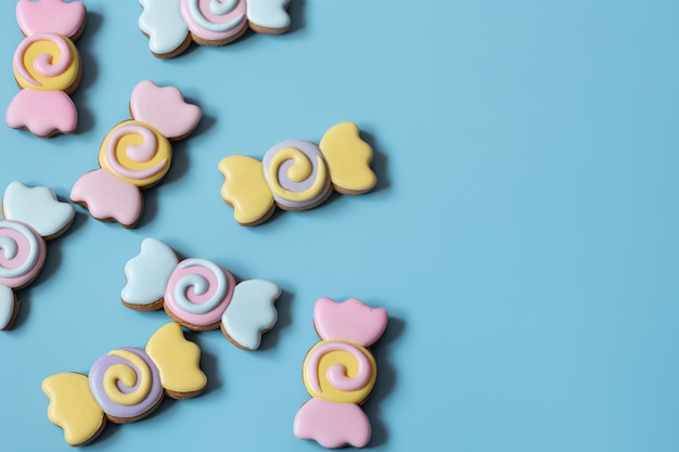 Colorful festive gingerbread cookies in the form of candies covered with glaze on a blue background copy space.