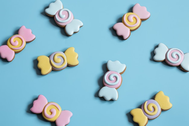 Colorful festive gingerbread cookies in the form of candies covered with glaze on a blue background.
