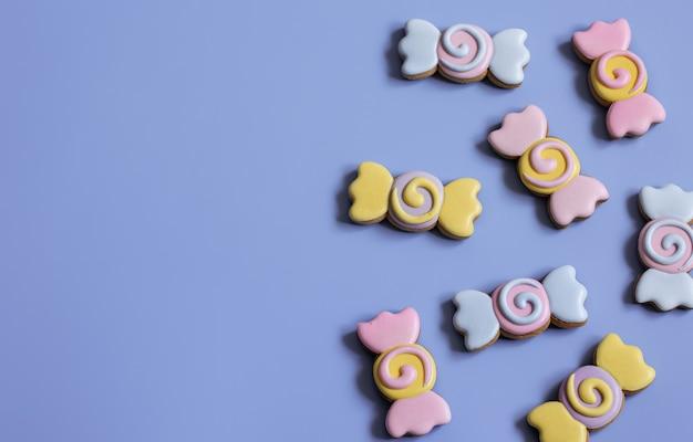 파란색 배경 복사 공간에 유약으로 덮인 사탕 형태의 다채로운 축제 진저 쿠키.