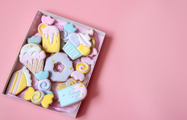 분홍색 배경 복사 공간에 유약으로 덮인 다양한 모양의 다채로운 축제 진저 쿠키.