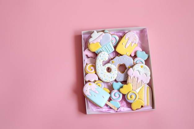 분홍색 배경에 유약으로 덮인 다양한 모양의 다채로운 축제 진저브레드 쿠키.