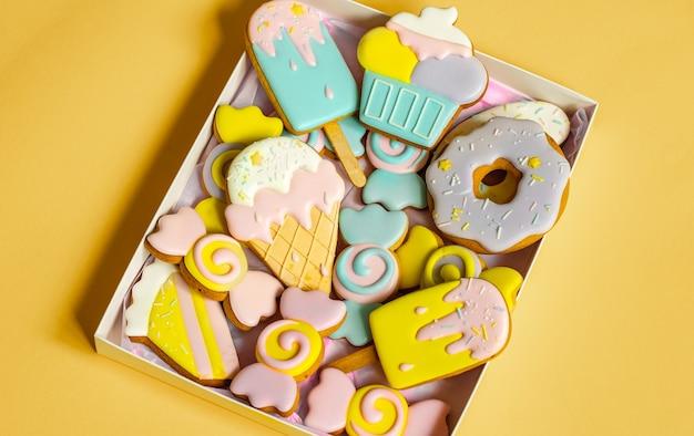 유약으로 덮인 다양한 모양의 다채로운 축제 진저 쿠키.