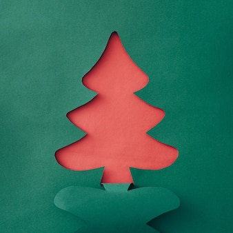 Colorful festive green and red template for a christmas card or poster with cutout shape of a traditional tree with copyspace for your holiday greetings