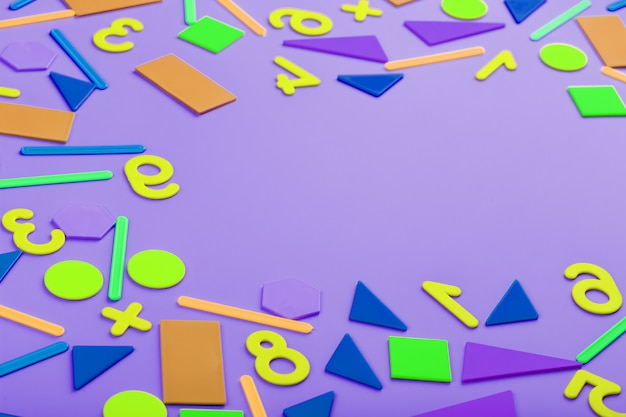 Colorful figures and numbers for children on a pink background. a tool for developing children's thinking.