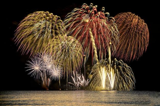 자정 하늘 배경으로 바다에서 화려한 불꽃놀이 축하.