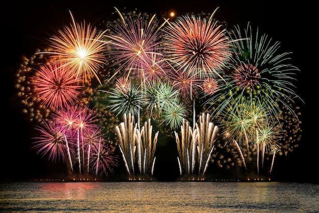 真夜中の空を背景に海からのカラフルな花火のお祝い。