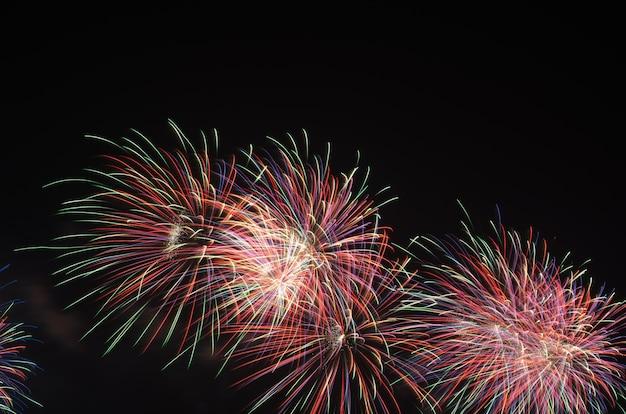 Красочные фейерверки на фоне черного неба над водой