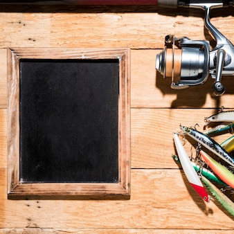 Colorful fishing baits; fishing reel near the blank slate on wooden desk