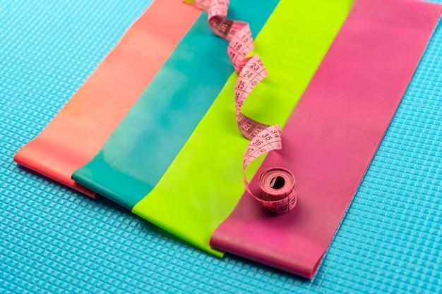 다채로운 피트니스 탄성 밴드와 분홍색 측정 테이프가 파란색 피트니스 매트에 놓여 있습니다.