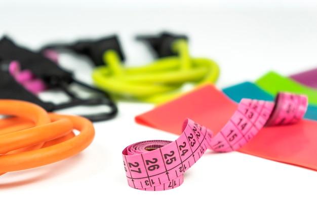 다채로운 피트니스 탄성 밴드 및 확장기, 흰색 바닥에 분홍색 측정 테이프 거짓말