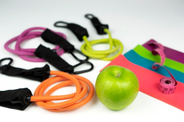 Colorful fitness elastic bands and expanders, a pink measuring tape lie on a white floor