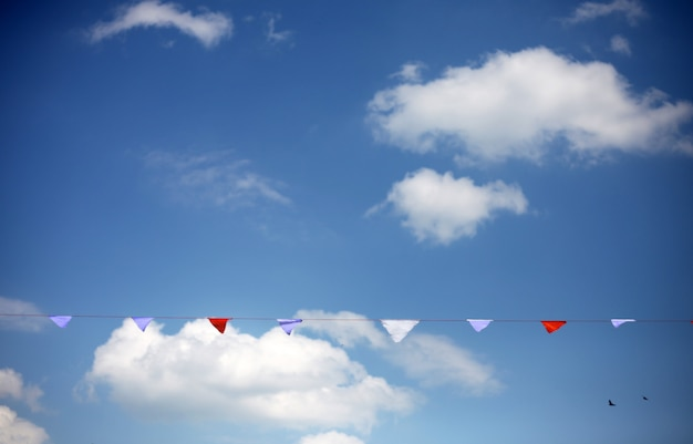 Colorful flags against blue sky with white clouds