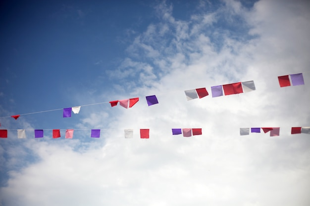 Colorful flags against blue sky with white clouds.