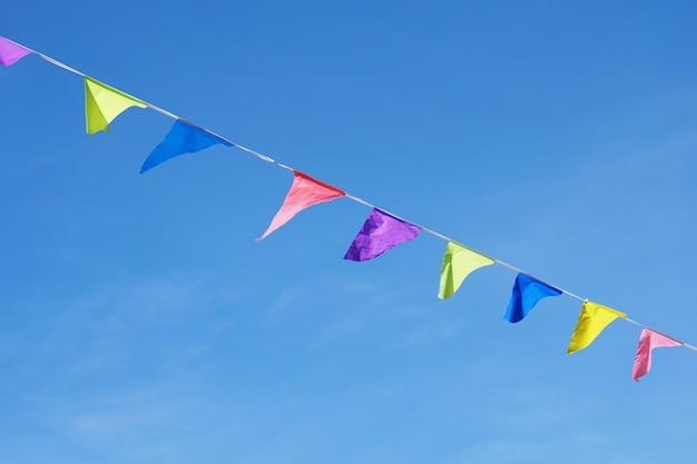青い澄んだ空の上のカラフルな旗