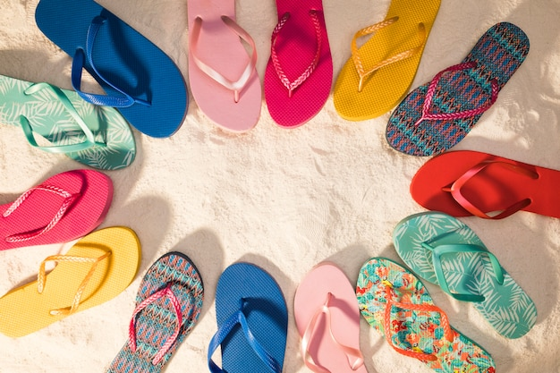 Colorful flip-flops on sand