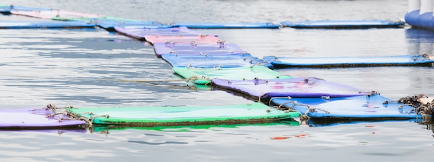 Colorful floating water mats or pads on water background