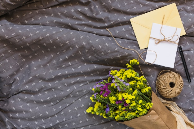 文字列スプールとカラフルな花の花束;カード;ペンと灰色の布に包む