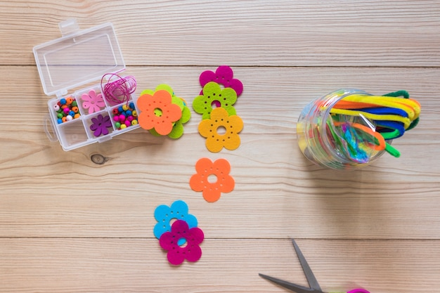 Colorful flower patch; chenille stems; and beads box on wooden backdrop