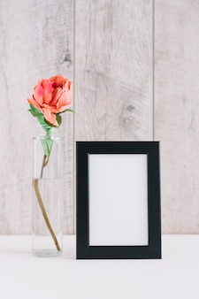 Colorful flower in vase near blank picture frame on table