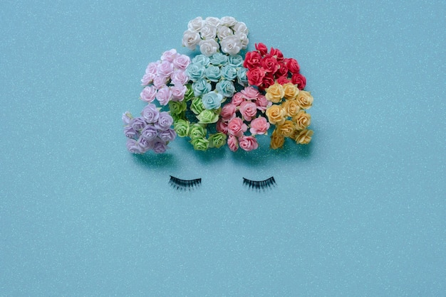 Разноцветные цветы и ресницы ровно лежат на синем фоне, образуя человеческое лицо.