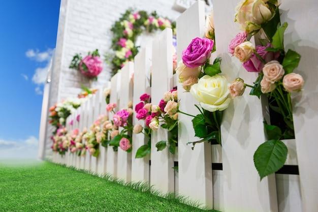 Разноцветные цветы у садовой ограды