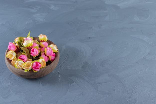 Fiori colorati in una ciotola, su fondo bianco. foto di alta qualità