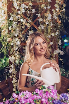 Colorful flowers in front of smiling young woman holding white watering can