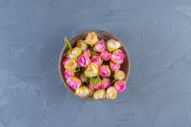 Красочные цветы в миске, на белом фоне.