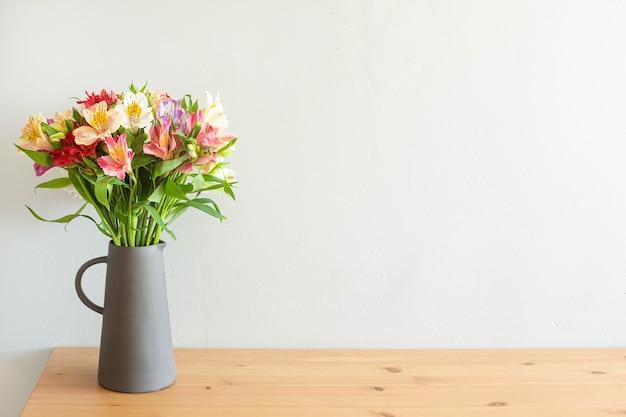 木製のテーブルの上のセメントの花瓶のカラフルな花