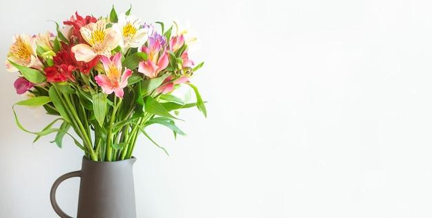 Красочные цветы в цементной вазе на деревянном столе