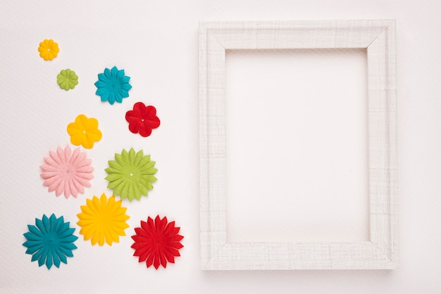Colorful flowers near the white wooden frame isolated on background