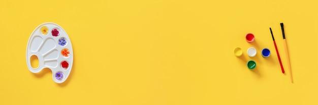 芸術的なパレット、ブラシ、黄色の背景にガッシュ、コピー領域に色とりどりの花。創造的なコンセプトの夏の色