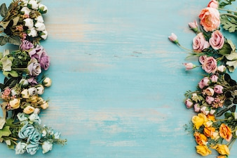 Colorful flowers on blue light wooden background.