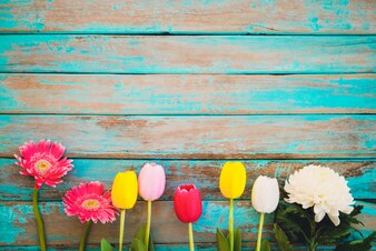 Colorful flowers on vintage wooden background, top view