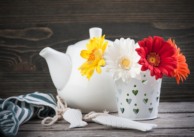 Colorful flowers and teapot on dark wooden surface