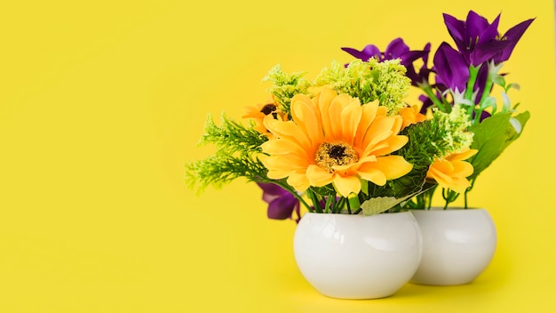 Colorful flowers in the white small vase against yellow background