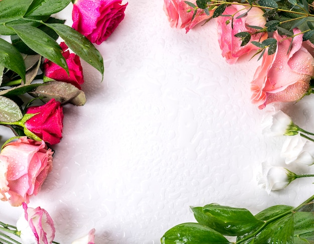 白いテーブルの上に水滴と色とりどりの花。