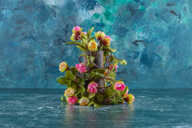 Colorful flowers in a wooden jug , on the blue background.