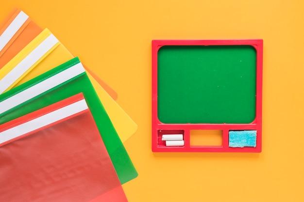 Красочные папки и маленькая зеленая доска