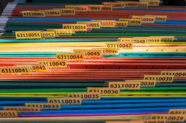 カラフルなフォルダーがファイルキャビネットに配置されています。
