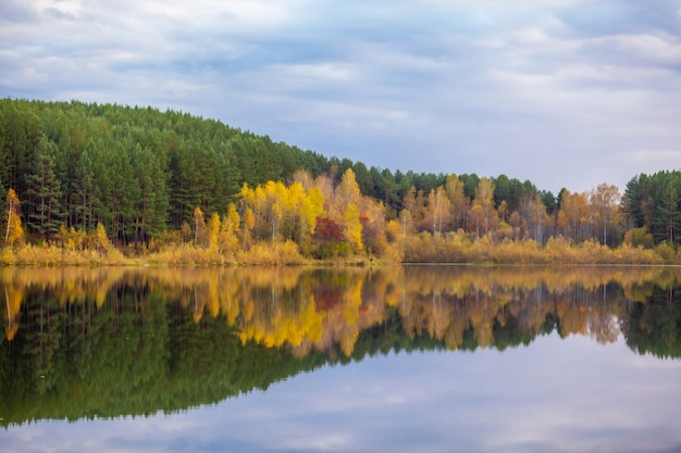 Colorful foliage tree reflections in calm pond water on a beautiful autumn day. a quiet and beautiful place to relax.