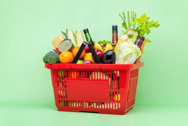 カラフルな食べ物や赤いスーパープラスチックバスケットの食料品